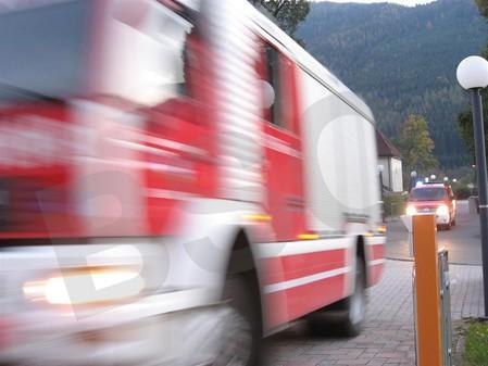 Dynamische Fotoaufnahme eines gerade ankommenden und durch die Geschwindigkeit am Foto verschwommen dargestellten Feuerwehr-Löschfahrzeugs und dahinter einem Mannschaftstransportfahrzeugs im Rahmen ei