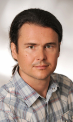 Portraitfoto von Baumeister Dipl.-Ing. Florian Hörri im dunklen Sakko mit dunklen und nach hinten gebundenen Haaren, leicht schmunzelnd