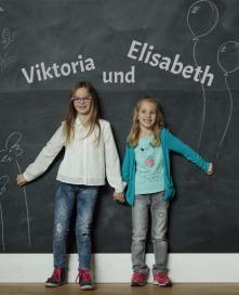 Seitliche Fotoaufnahme der beiden zueinander sehenden Töchter von Manuela und Rudolf Mark, Viktoria und Elisabeth im lila-weiß-karierten Kleid