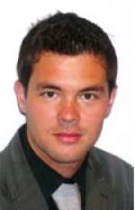 Portraitfoto von Mag. Christian Hörri im dunkelgrauen Sakko mit schwarzem Hemd und hellgrauer Krawatte, dichtes dunkelbraunes Haar, leicht schmunzelnd