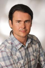 Portraitfoto von Baumeister Dipl.-Ing. Florian Hörri, Geschäftsführer der BSC Brandschutzconsult Bautechnik GmbH (helles kariertes Hemd, dunkle Haare nach hinten gebunden) / Spezialist Bauwesen