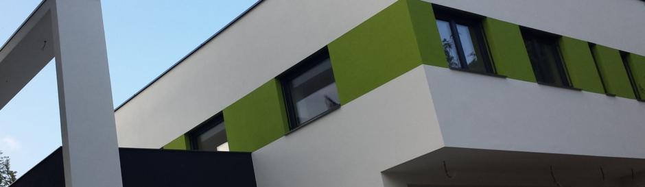 Bildausschnitt moderne Villa mit weiss-grüner Fassade und Design-Rahmen über der Terrasse